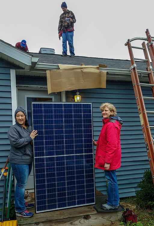 This is a picture of Tora Knapp and Stephanie Kimball handing a solar panel to volunteers on the roof.