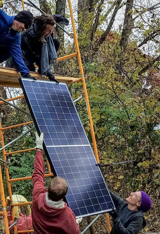 This is a picture of several volunteers raising a solar panel on a roof.