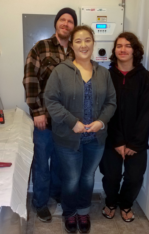 This is an image of the Knapp family standing by a solar inverter they installed and activated.