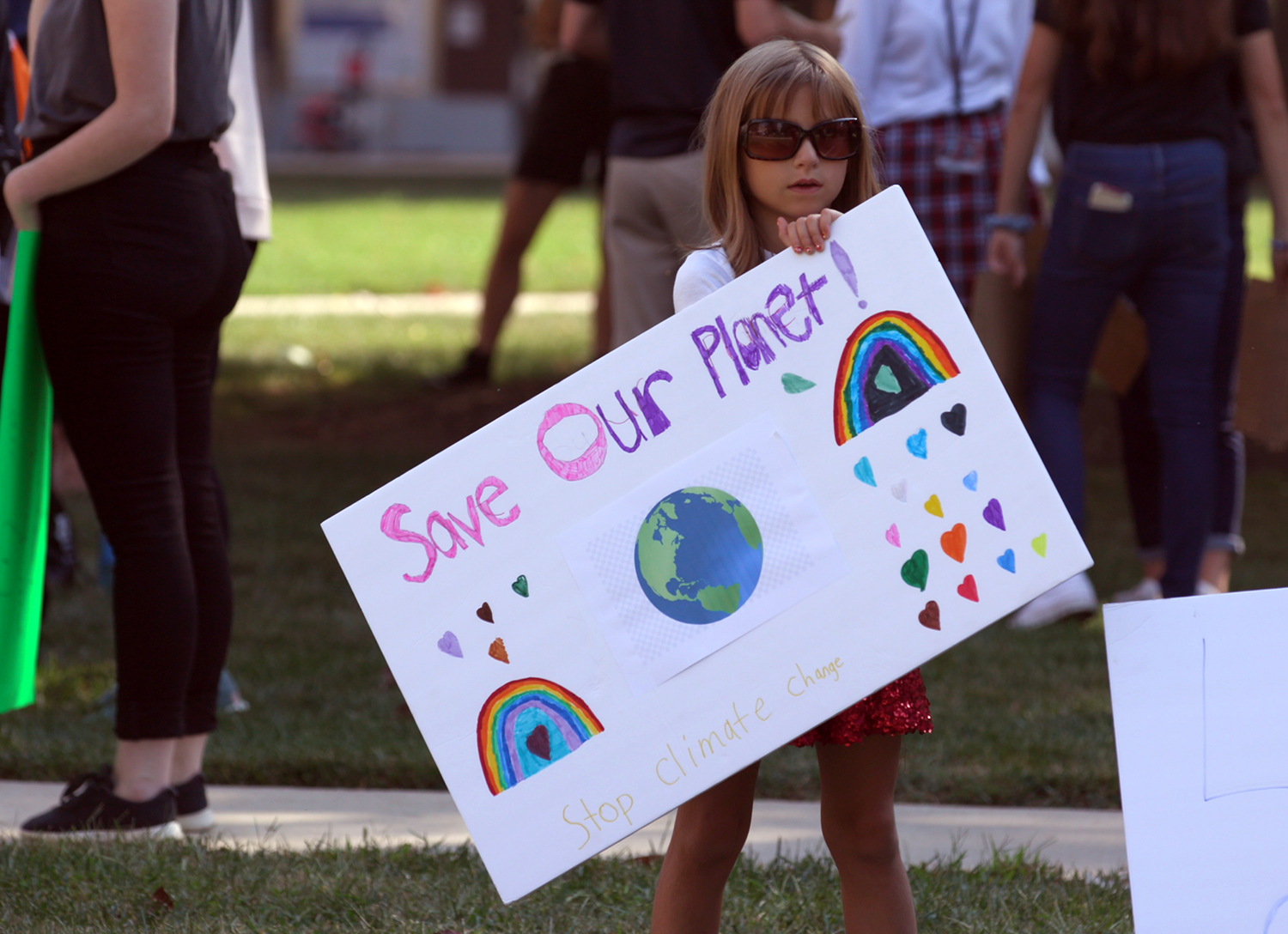 """This is a photo of a child holding a sign with the message, """"Save our planet."""""""