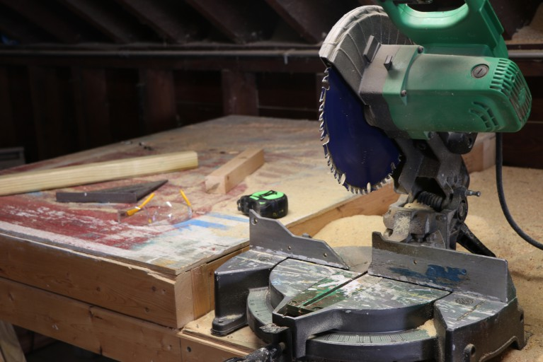 A green power saw on a work bench