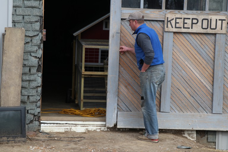 A man closing the door which reads keep out